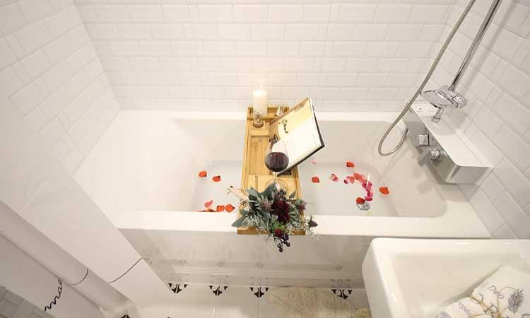 Bañera con repisa y flores.