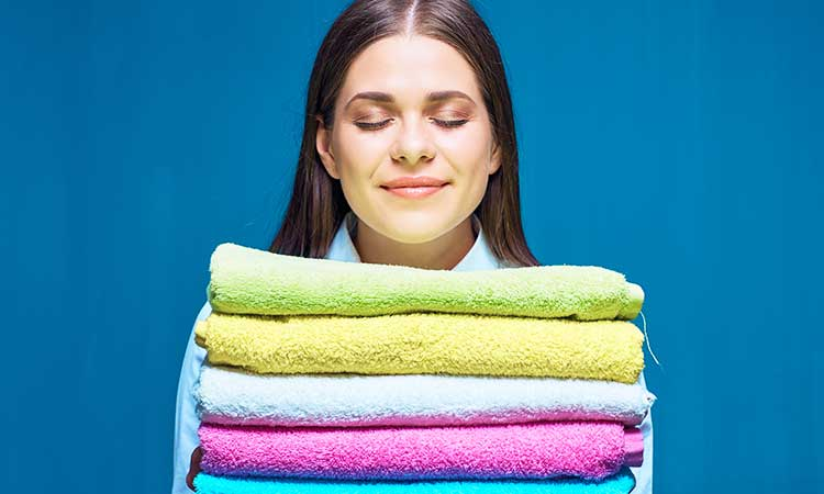 Good smelling laundry without fabric softener, woman smells fresh laundry