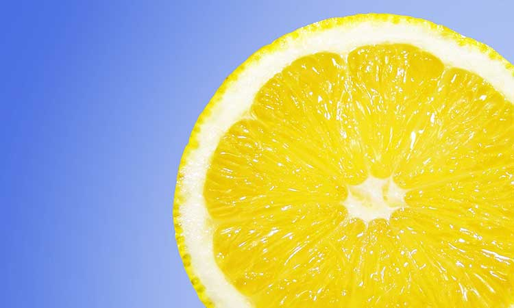 Descaling kettle with citric acid, lemon in front of blue background