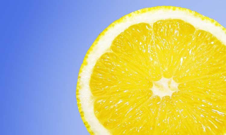 Hervidor de descalcificación con ácido cítrico, limón delante de un fondo azul