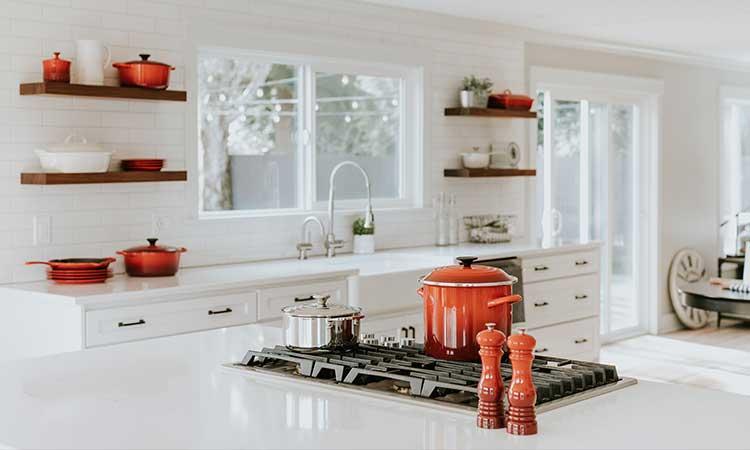 weiße Küche mit roten Farbelementen, Töpfen