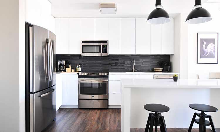 Klassisch weiße Küche, schwarze Barhocker