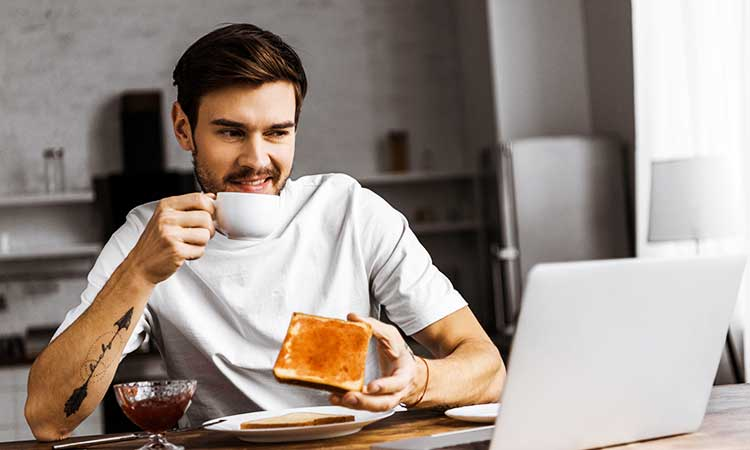 man working from home while having coffee and toast